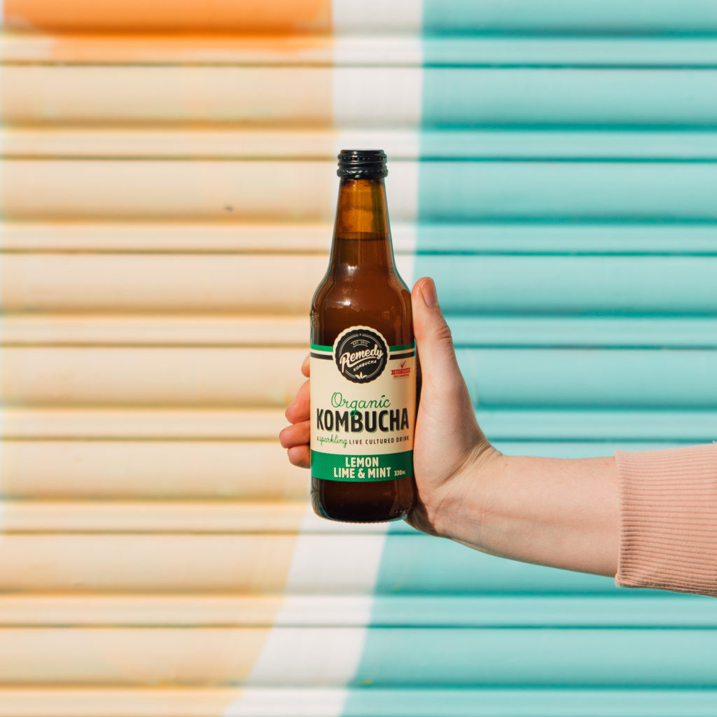 Remedy Lemon Lime and Mint Kombucha in front of pastel wall